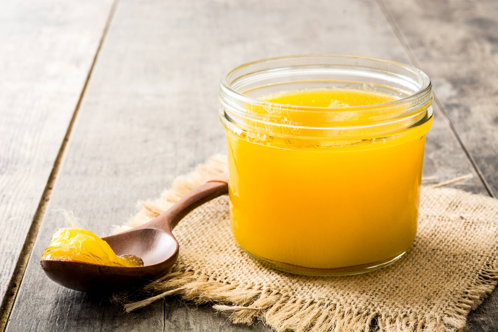 Ghee or clarified butter in jar and wooden spoon on wooden table. |  |